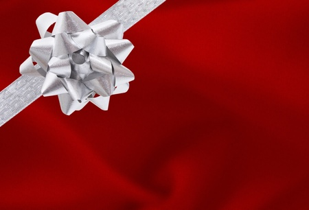 A red present with a silver ribbon and bow with copy space
