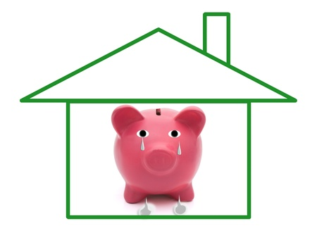 A green outline of a house with a sad piggy bank, Home Foreclosures photo