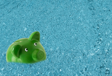 A green piggy bank sinking in water, Drowning in debt Stock Photo