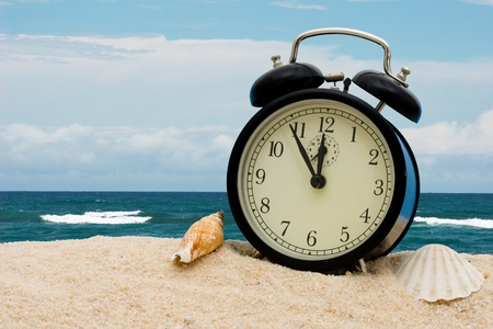 An alarm clock with seashells sitting on the sand with water, vacation time photo
