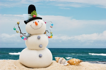 A snowman with seashells sitting on the sand with water, winter vacation