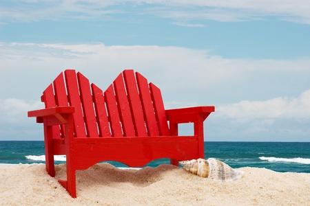 Een houten strandstoel zittend op het zand met water, strandstoel Stockfoto - 8989506