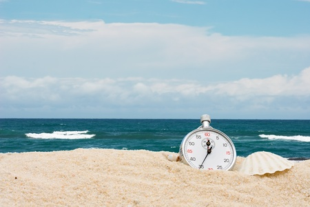A stopwatch with seashells sitting on the sand with water, vacation time