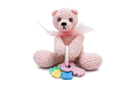 Homemade crochet teddy bear with a baby rattle, having a baby photo