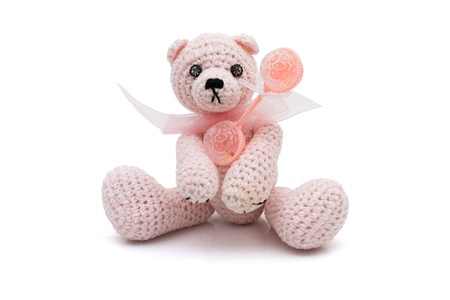 Homemade crochet teddy bear with a baby rattle isolated on white Stok Fotoğraf - 9354691