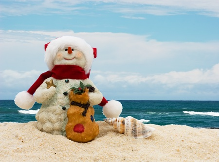 A snowman with bag the sand at the beach, Winter vacation getaway