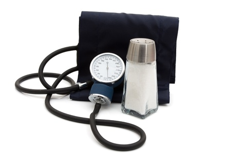 cuffs: A blood pressure reading device, Sphygmomanometer isolated on white with a salt shaker Stock Photo