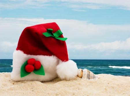 pascuas navideÑas: Un sombrero de Navidad la arena en la playa, estancia de vacaciones de invierno Foto de archivo