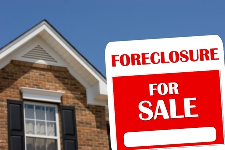 foreclosure: A red and white for sale sign with a brick house in background
