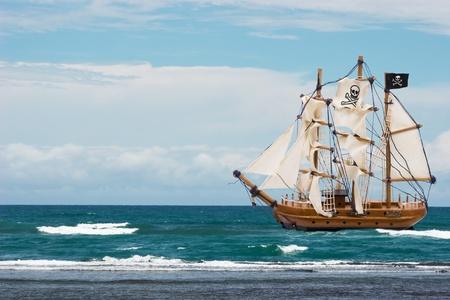 barco pirata: Un barco pirata con bandera negra en el océano, barco pirata Foto de archivo