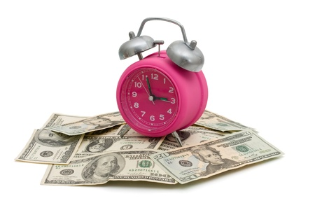 Pink alarm clock on some American money isolated on white, Time to save money photo