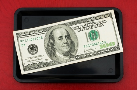 gratuity: A one hundred dollar bill on a black tray on a wood background, tip money Stock Photo