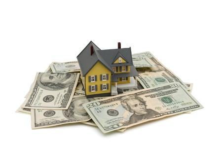 equidad: Casa amarilla en dinero estadounidense aislada sobre fondo blanco, invertir en una casa