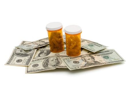 health equity: Pill bottles with pills on some American money isolated on white, Cost of healthcare Stock Photo