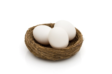 Three white eggs in a nest isolated on a white background photo