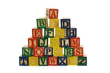 カラー白、学校日の間で分離されたアルファベットの木製のブロックをスタック