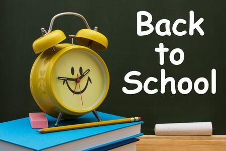 Libro con l�piz y goma de borrar con un reloj despertador retro frente de una pizarra, regresar a la escuela Foto de archivo - 10169945
