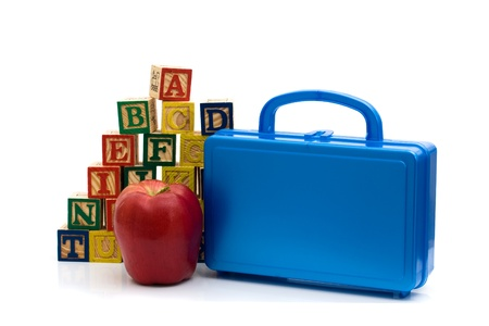 A lunch box and apple in front of color wooden blocks of the alphabet isolated over white, Schools Lunches photo