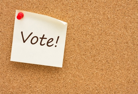 A sticky note on a corkboard with the words vote on it Stock Photo - 10287460