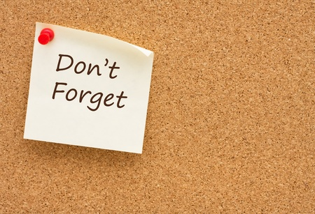 thumb tack: A sticky note on a corkboard with the words don�t forget on it