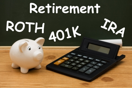 A piggy bank with calculator and chalk on a chalkboard with word retirement, Understanding your retirement  Stock Photo