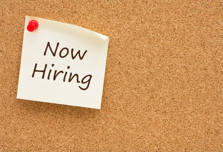 help: A sticky note on a cork board with the words now hiring on it