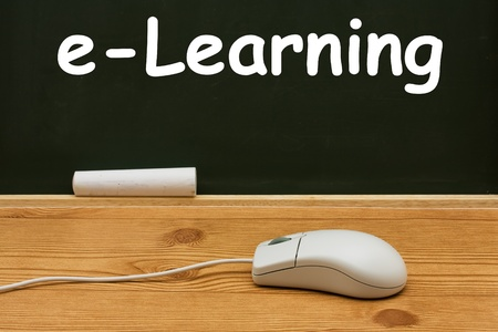 study: Computer mouse on a desk in front of a chalkboard with copy space, E-learning Stock Photo