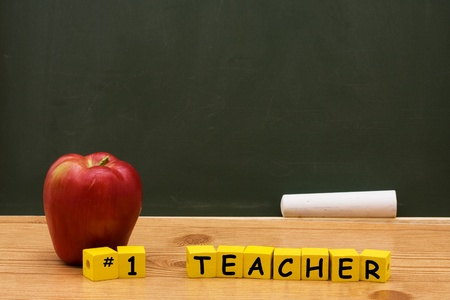 An apple and yellow block with number one teacher on them in front of a chalkboard with copy space, Best Teacher Stock Photo