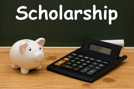 scholarship: A piggy bank with calculator and chalk on a chalkboard with word Scholarship, Education Scholarship Stock Photo