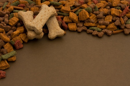 A border made of dog food and dog treats on brown background, dog food Imagens