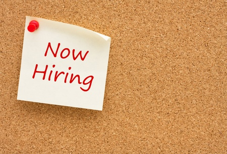 job advertisement: A sticky note on a cork board with the words now hiring on it
