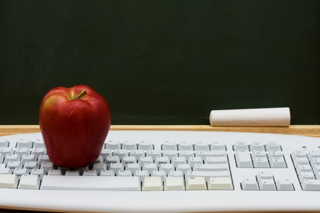 home schooling: Computer keyboard on a desk with an apple in front of a chalkboard with copy space, E-learning