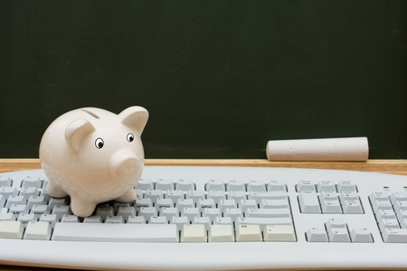 Computer keyboard on a desk with a piggy bank in front of a chalkboard with copy space, Cost of learning online photo