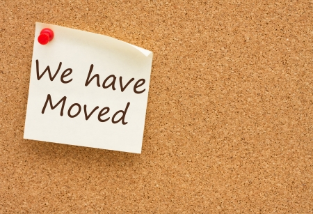 on the move: A sticky note on a cork board with the words we have moved on it Stock Photo