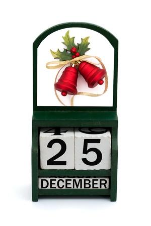 calendario diciembre: Un calendario de madera con una fecha de 25 de diciembre y campanas rojas, feliz Navidad Foto de archivo
