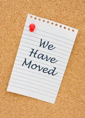 moved: A torn notepad paper on a cork board with the words we have moved on it Stock Photo