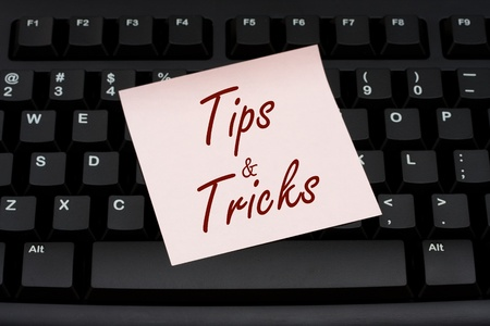 tip: Computer keyboard with a pink sticky note with text tips and tricks, Tips and Tricks Stock Photo