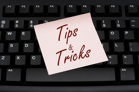 Teclado de ordenador con una nota rosa con texto y trucos, consejos y trucos