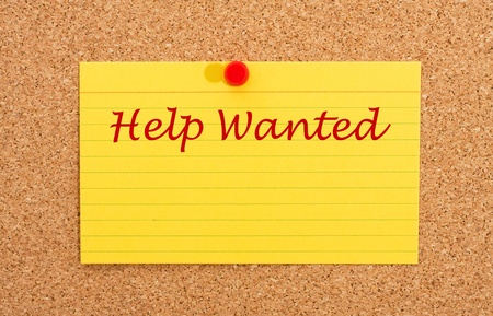 A yellow index card on a cork board with the words help wanted on it Stock Photo - 10727633