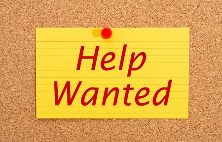 A yellow index card on a cork board with the words help wanted on it photo
