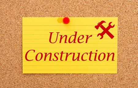 A yellow index card on a cork board with the words under construction on it Stock Photo - 10834022