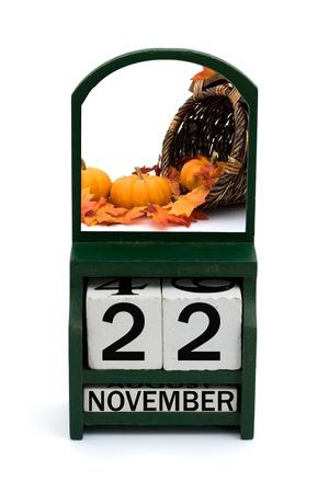 calendario noviembre: Un calendario de madera con una fecha de 22 de noviembre y calabazas, feliz Thanksgiving
