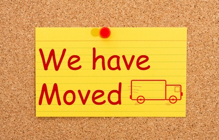 moved: A yellow index card on a cork board with the words we have moved on it Stock Photo