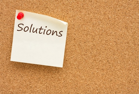 A yellow sticky note on a cork board with the word Solutions on it Stok Fotoğraf