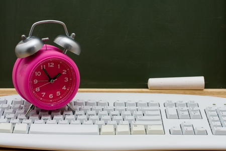 home schooling: Computer keyboard on a desk with an alarm clock in front of a chalkboard with copy space, Time to get an education online