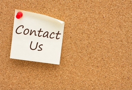 contact: A yellow sticky note on a cork board with the words Contact Us on it