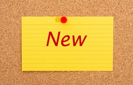 A yellow index card on a cork board with the word new on it, Announcing something new Stock Photo - 11011264