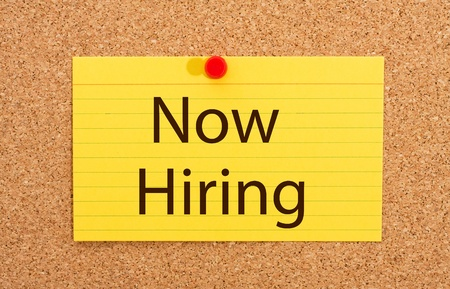A yellow index card on a cork board with the words now hiring on it