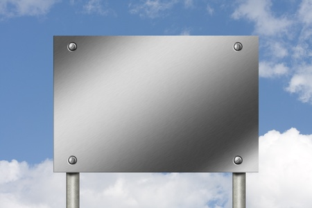 Brushed steel sign with screws with plenty of copy space for your message with a clear blue sky background