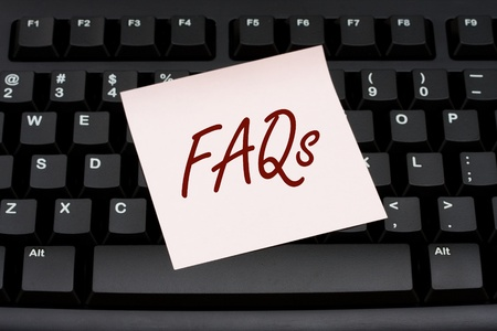 faq's: Computer keyboard with a pink sticky note with text FAQs, Computer FAQs Stock Photo